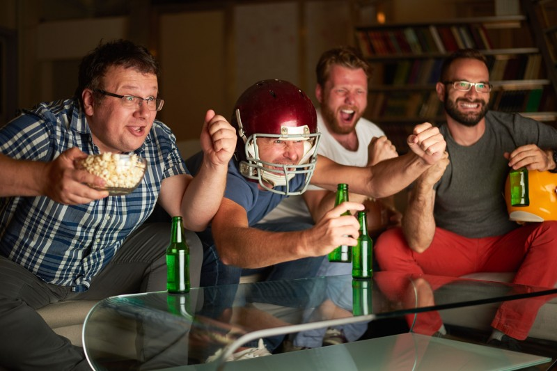 86577729 - four friends watching game of american football on television