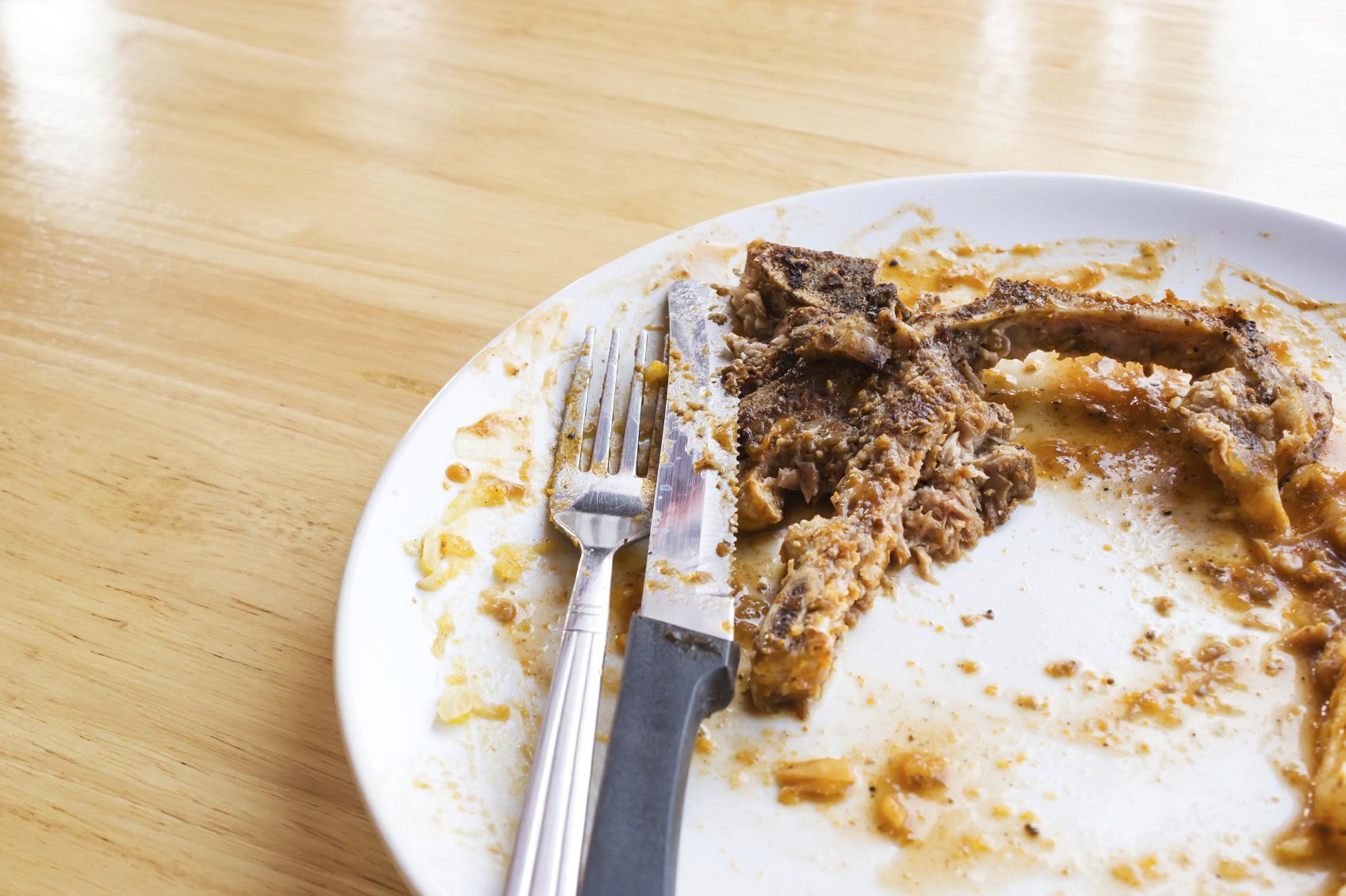 T-bone steak leftover on white plate.