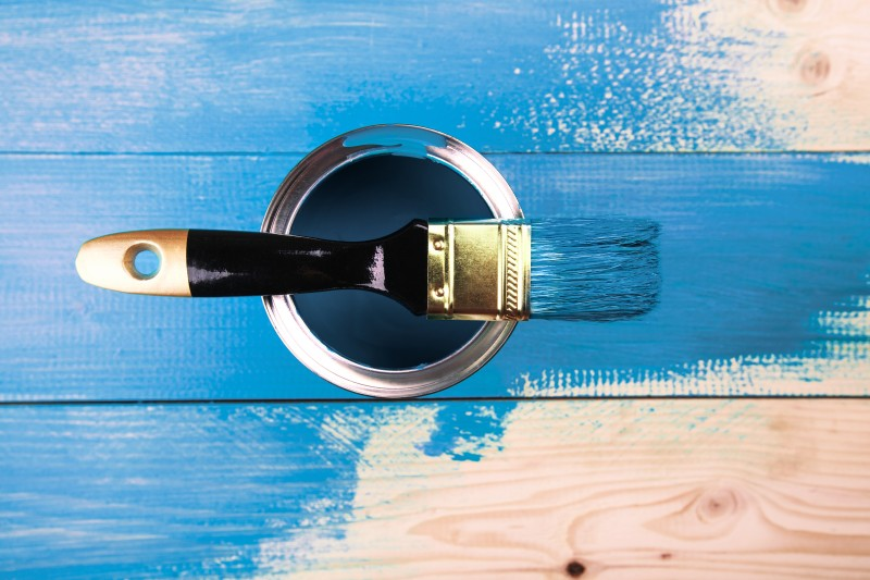 Painting a wooden shelf using paintbrush
