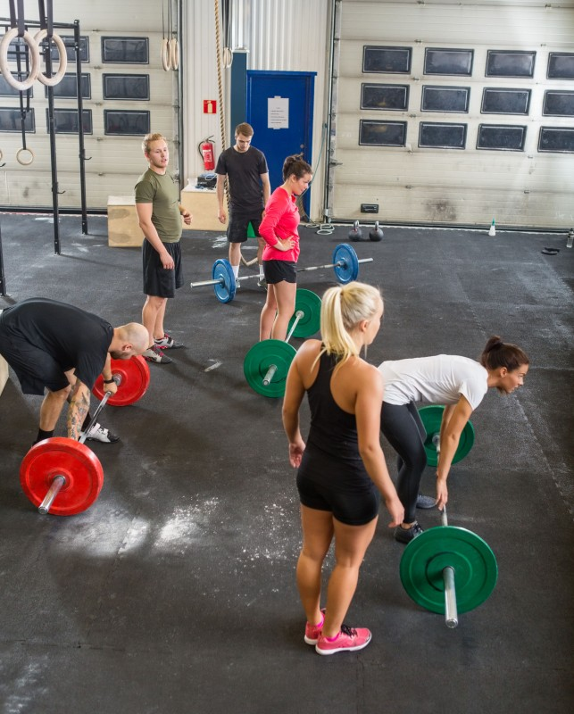 35442239 - trainers with athletes lifting barbells