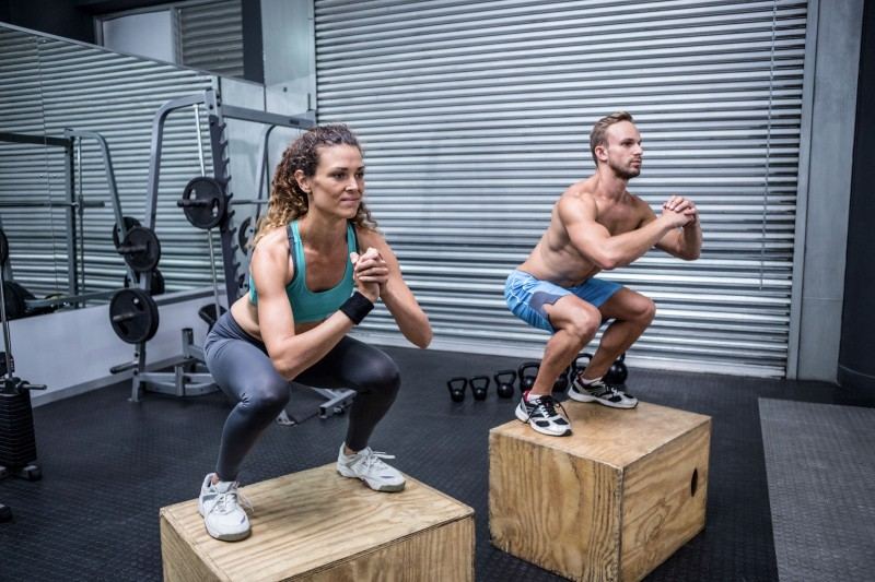 42327116 - muscular couple doing jumping squats on a wooden box