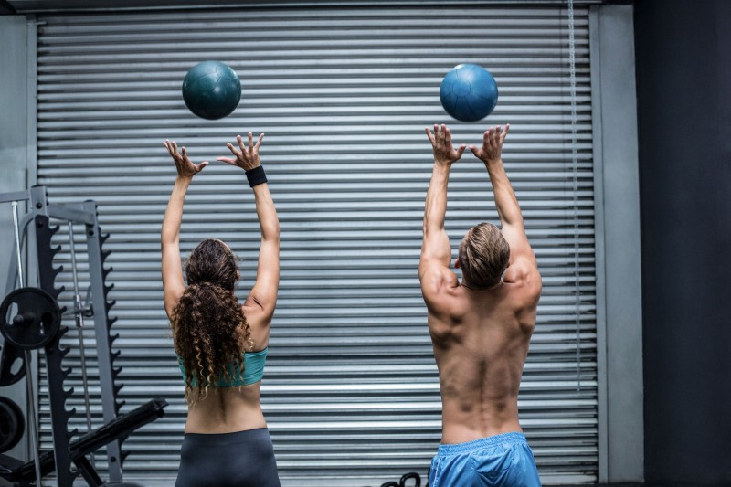 42327141 - back view of a muscular couple throwing ball in the air