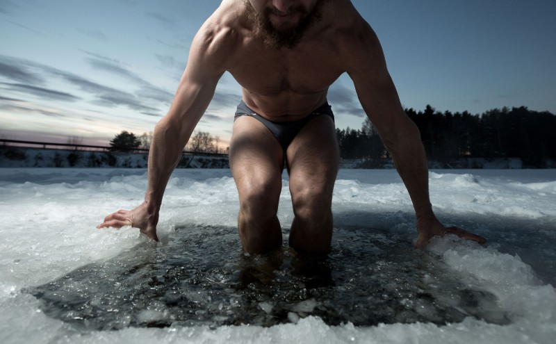 35423462 - young man having recreational swim in the ice hole