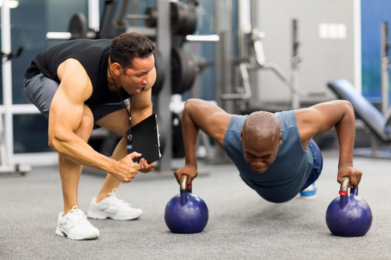 personal trainer motivates client doing push-ups