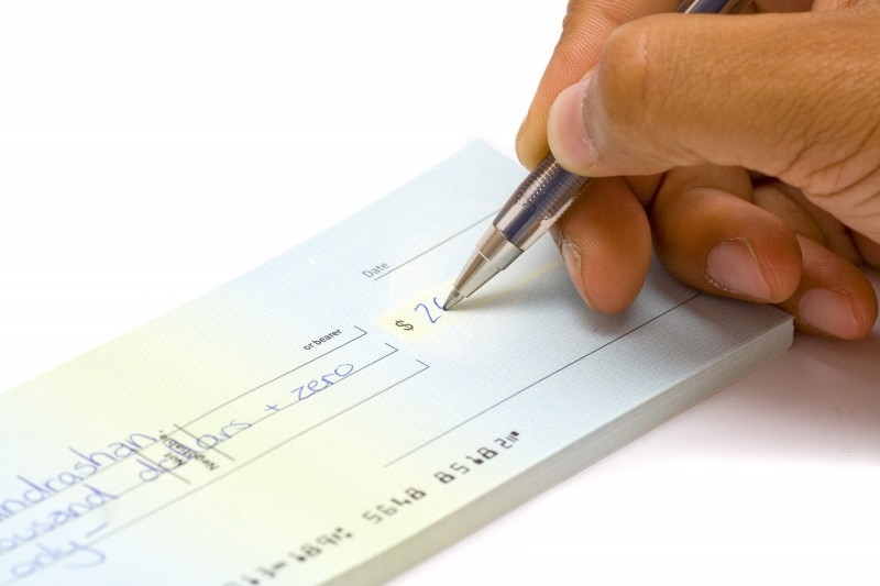 14918371 - a hand signing a cheque