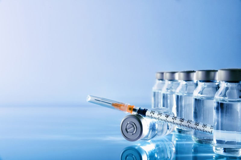 Vials group and syringe on table with blue background