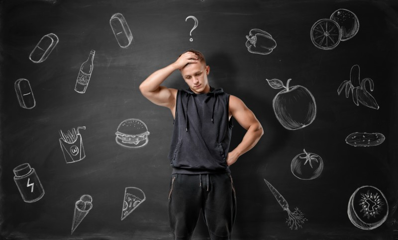 Muscled young man pondering on what to choose: junk or healthy food