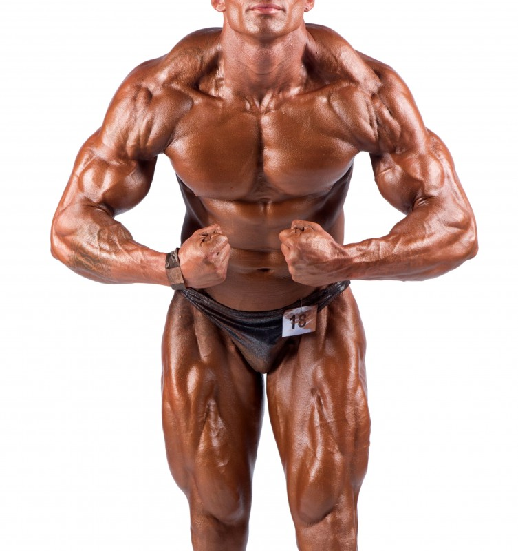 12668112 - bodybuilder flexing his muscles in studio