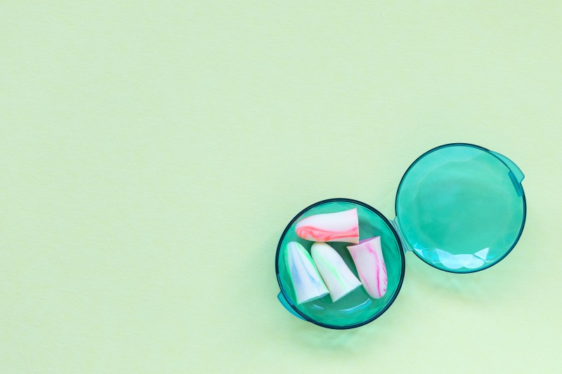Earplugs in a box on the green background. Good sleep and noise