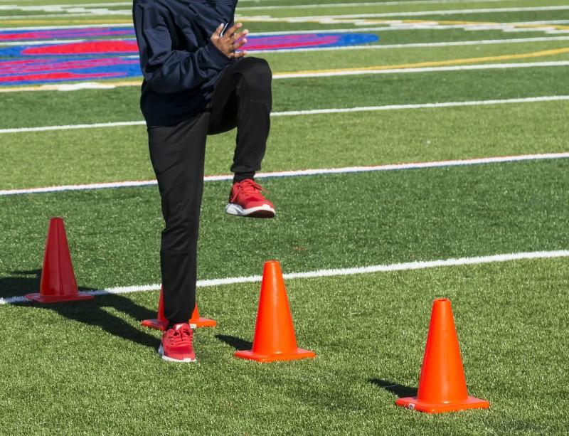 High school track athlete doing speed drills over cones