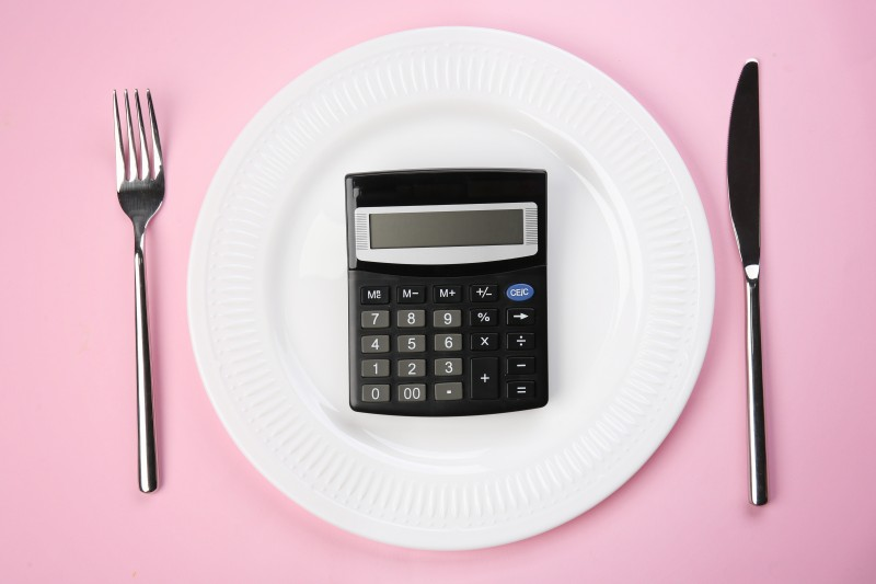 Diet concept. Plate with calculator and cutlery on color background