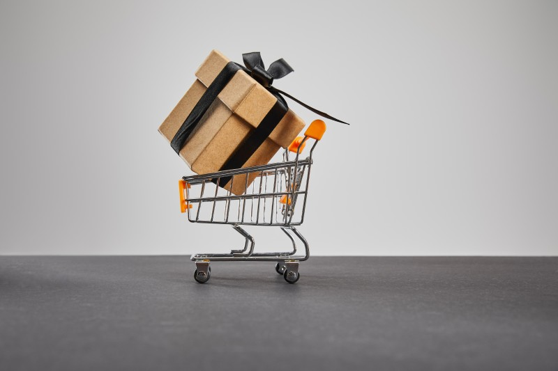 cardboard gift box with black ribbon in small shopping cart isolated on grey, black Friday concept