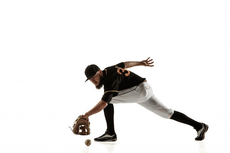Baseball player, pitcher in a black uniform practicing on a white background.